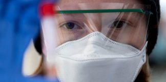 Person in face mask looking at test tube (Sven Hoppe/picture alliance via Getty Images)