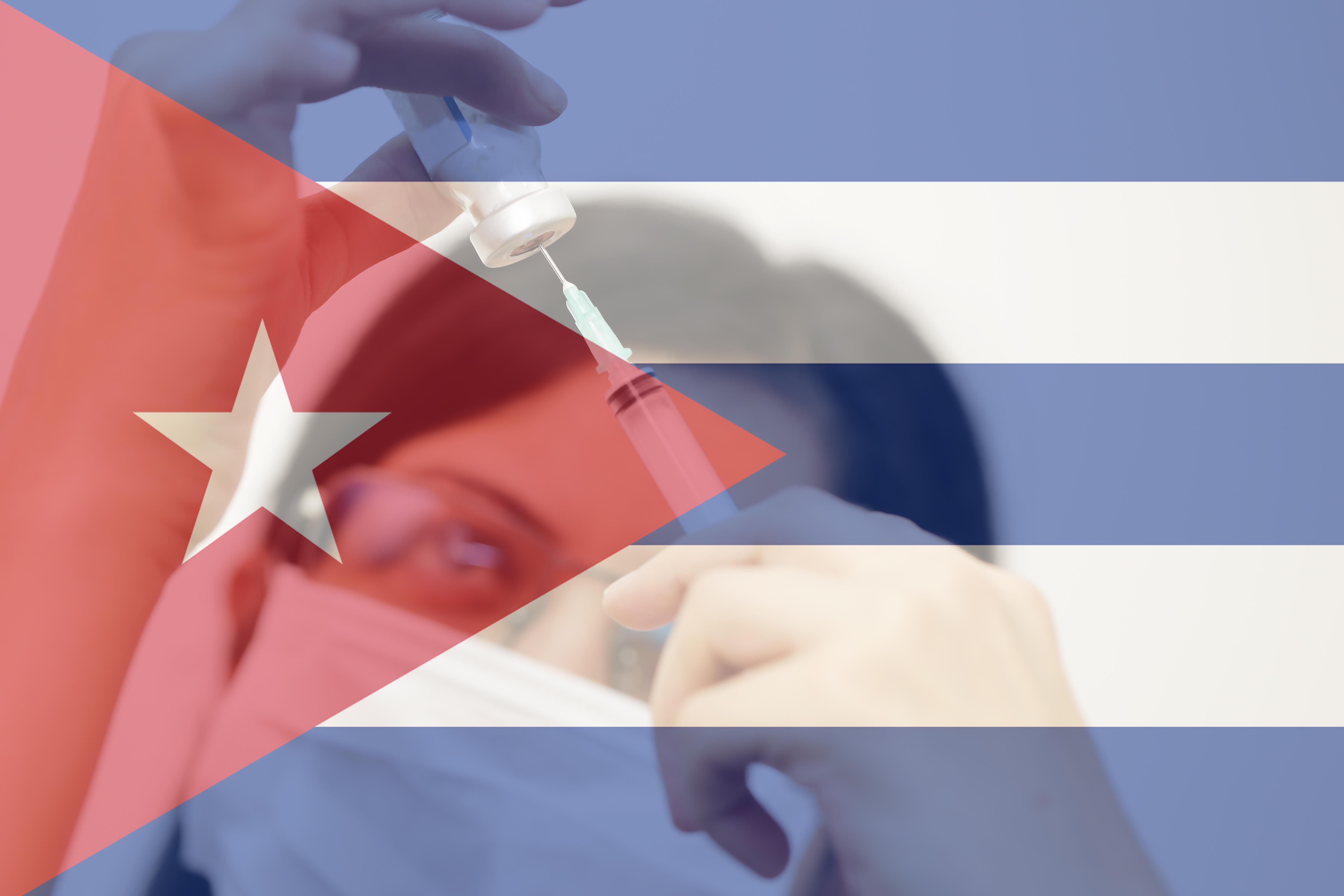 کیوبا کا جھنڈا اور چہرے پر ماسک لگائے سرِنج پر دیکھتی ہوئی ایک عورت۔ (© Shutterstock)