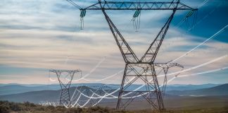 Electrical wires stretching across towers in field (© Shutterstock)