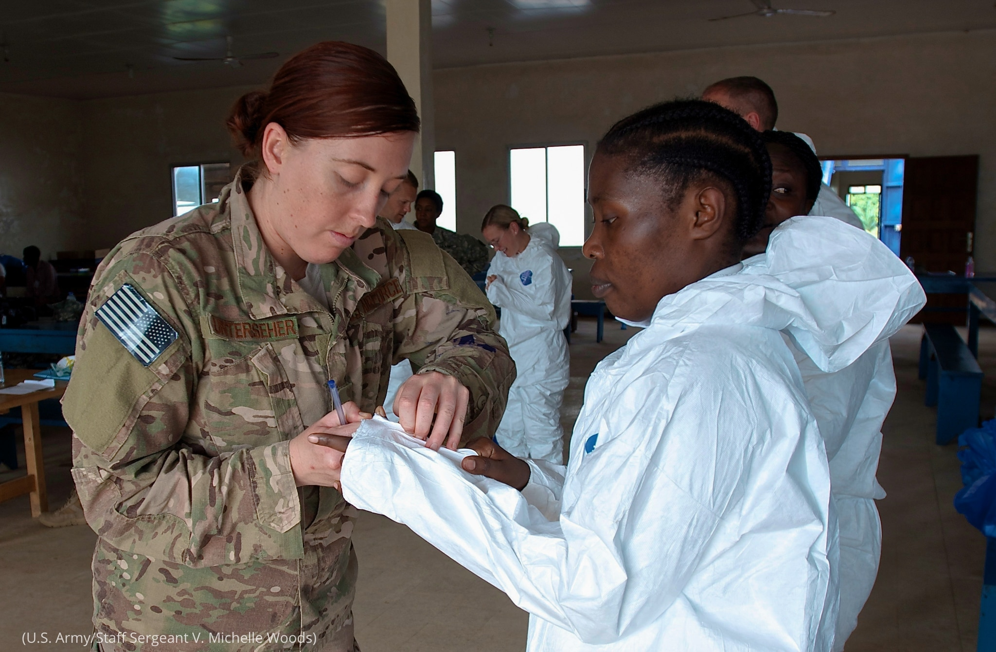 Woman in camouflage uniform helping another woman suit up in white protective garb (U.S. Army/Staff Sergeant. V. Michelle Woods)
