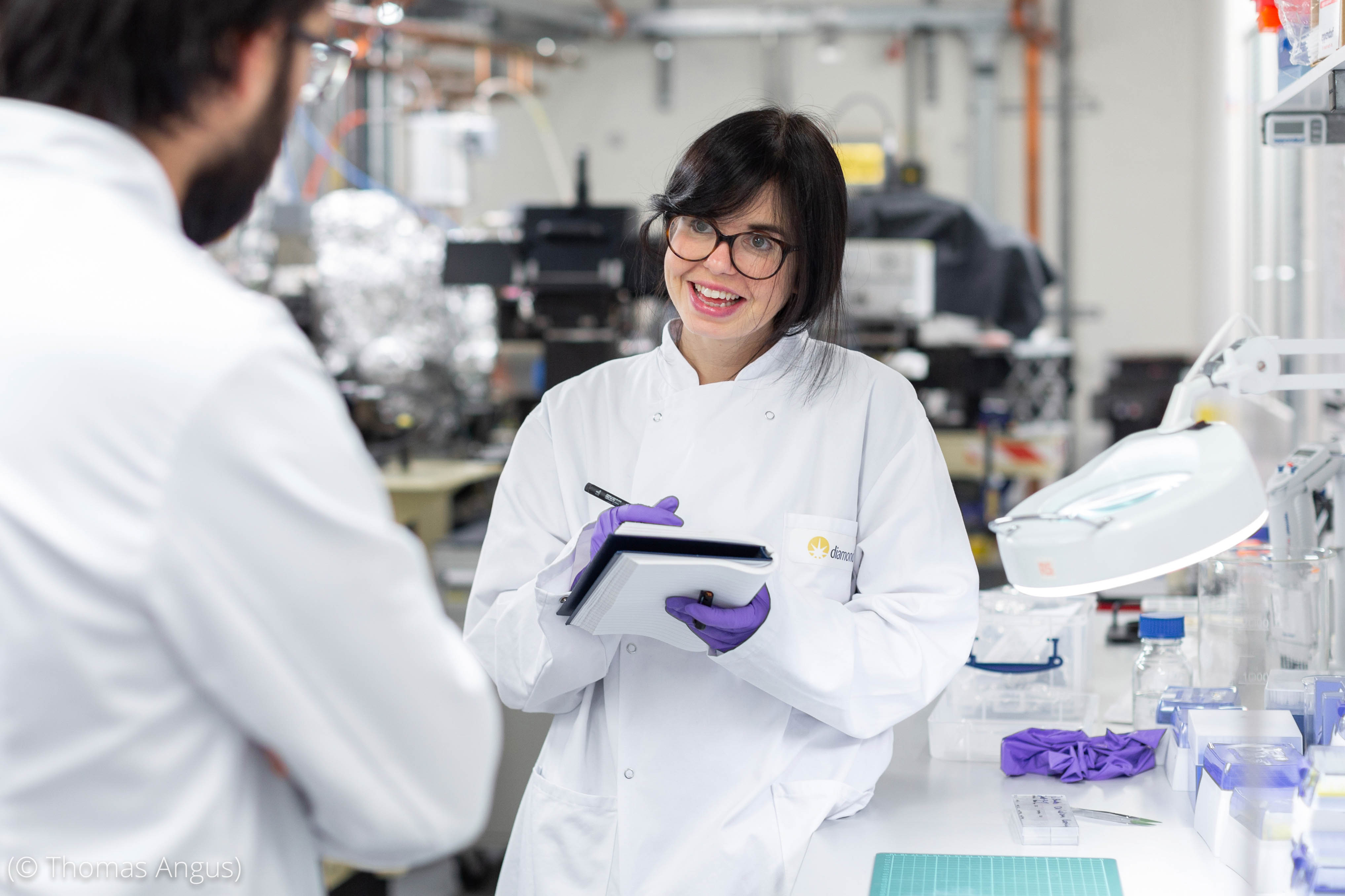 Woman in lab taking notes while talking to another person (© Thomas Angus)