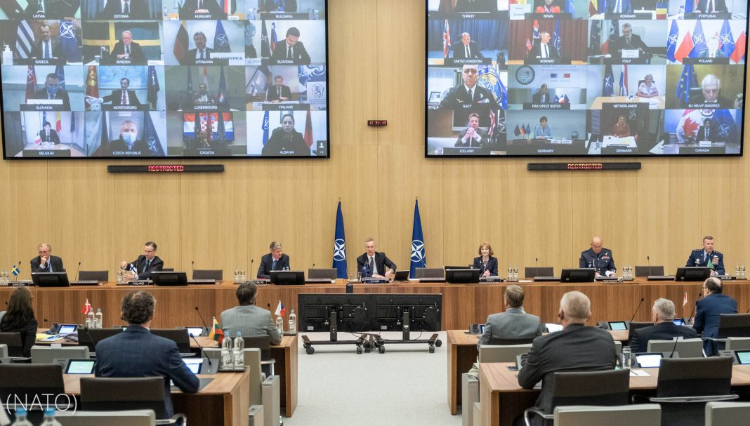 Meeting with participants showing on two large screens on wall (NATO)
