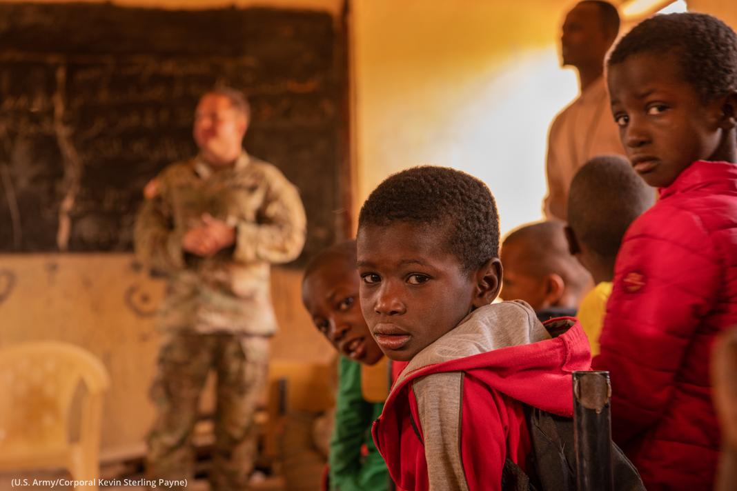 بچے پس منظر گفتگو کرتے ہوئے ایک آدمی کو سن رہے ہیں۔ (U.S. Army/Corporal Kevin Sterling Payne)