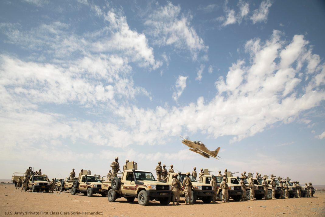 صحرا میں ٹرکوں کے سامنے فوجی جوان کھڑے ہیں اور ایک فوجی طیارہ پرواز کرتے ہوئے اُن کے سروں پر سے گزر رہا ہے۔ (U.S. Army/Private First Class Clara Soria-Hernandez)