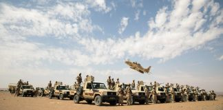 Trucks and military personnel in desert with military aircraft taking off overhead (U.S. Army/Private First Class Clara Soria-Hernandez)