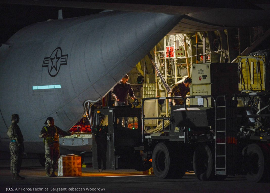 Des militaires en train d'embarquer des fournitures à bord d'un avion, de nuit (U.S. Air Force/Technical Sergeant Rebeccah Woodrow)