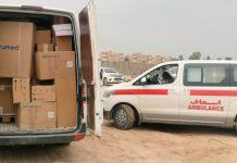 Des caisses dans une camionnette avec les portières arrière ouvertes, et une ambulance sur le côté (DVIDS/Photo offerte)