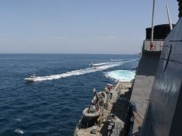 Small vessels sailing close to larger ship (U.S. Navy)