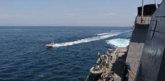 ایک بڑے جہاز کے قریب سے گزرتی ہوئی چھوٹی کشتیاں۔ (U.S. Navy)