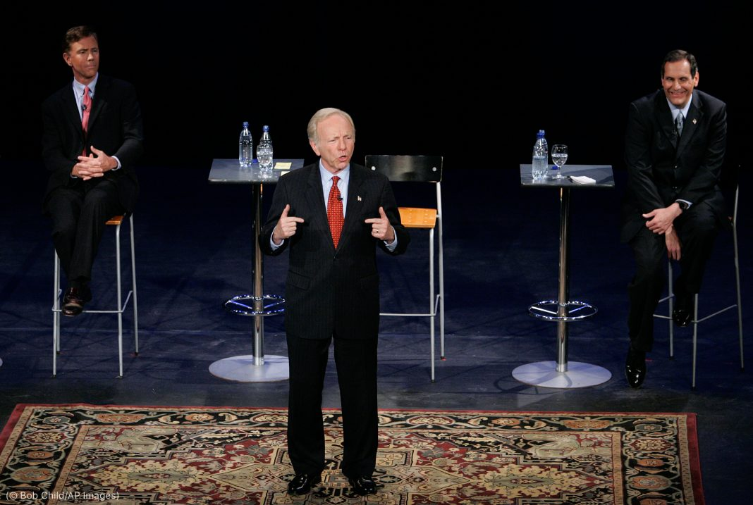 Man speaking while standing, flanked by two men sitting in the background (© Bob Child/AP Images)