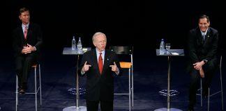 کھڑا ہوا ایک آدمی تقریر کر رہا ہے اور اس کے پیچھے دونوں طرف دو آدمی بیٹھے ہوئے ہیں۔ (© Bob Child/AP Images)