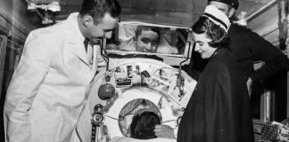 Un patient atteint de polio dans un poumon d'acier, entouré de personnel médical (© AP Images)