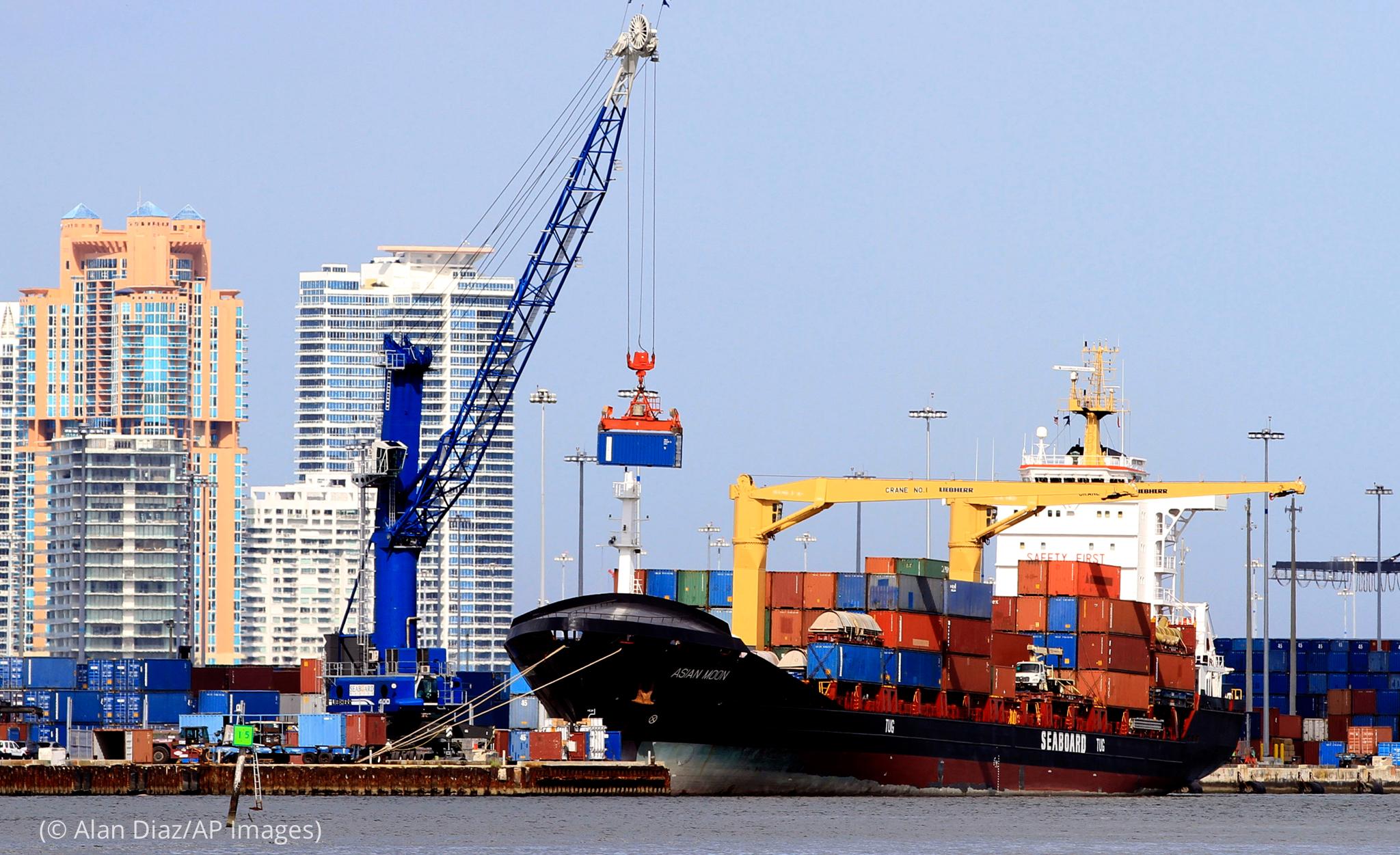 吊车把集装箱装载在货轮上(© Alan Diaz/AP Images)