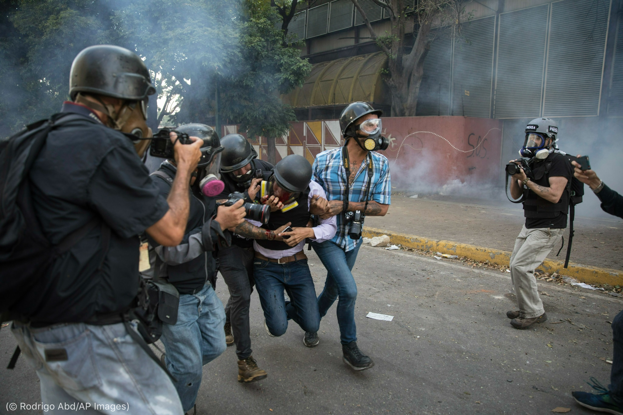 Des photographes équipés de casques et de masques à gaz portant un collègue blessé (© Rodrigo Abd/AP Images)