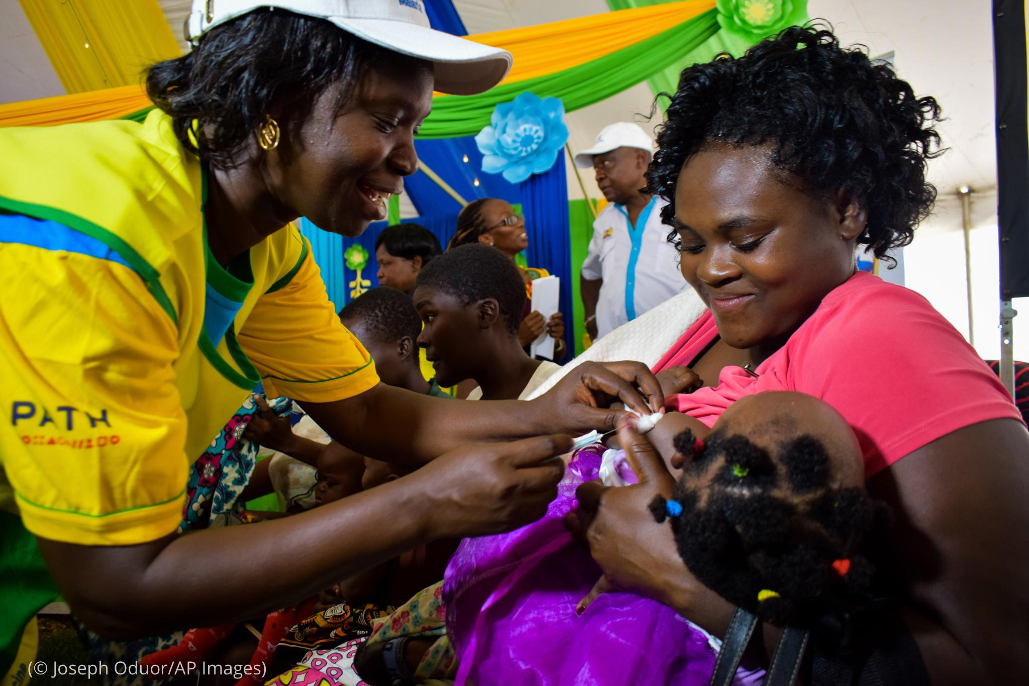 ماں کے بازوؤں میں پکڑے ایک بچے کو ایک خاتون ٹیکہ لگا رہی ہے۔ (© Joseph Oduor/AP Images