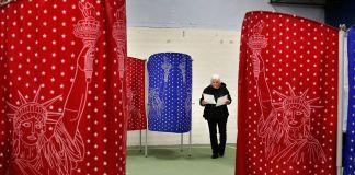 Wanita melihat ke surat suara saat berjalan melewati bilik suara berwarna-warni (© Robert F. Bukaty/AP Images)