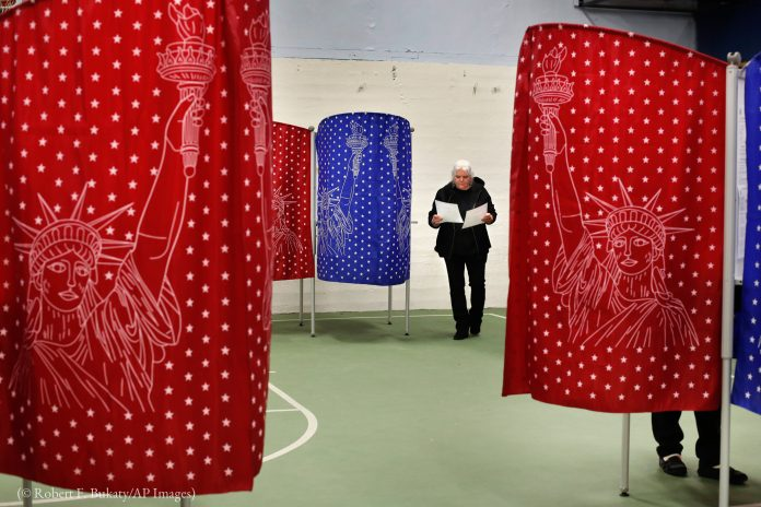 Woman walking past colorful voting booths