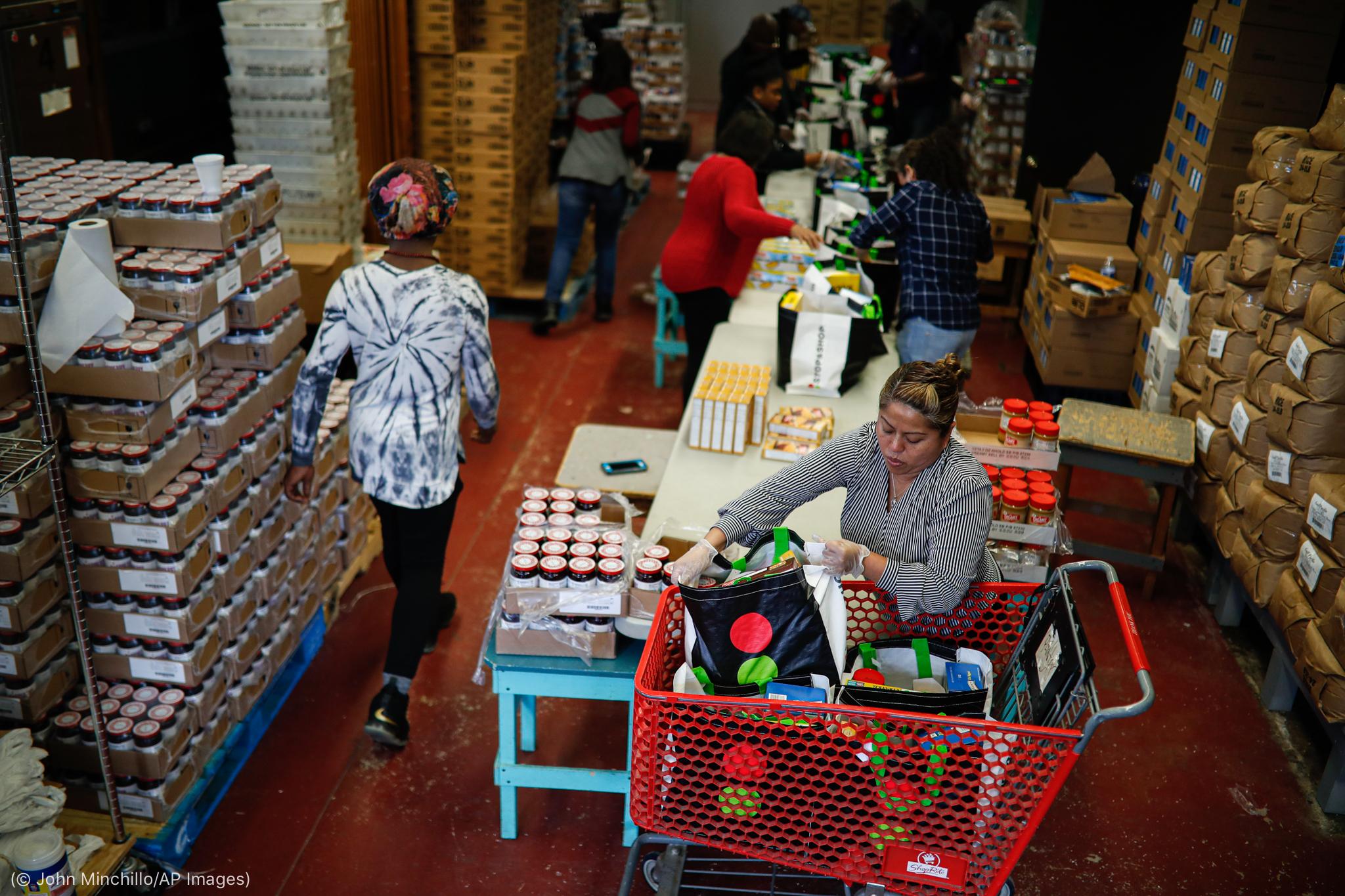 Sejumlah orang mengemas barang di samping tumpukan bahan makanan (© John Minchillo/AP Images)