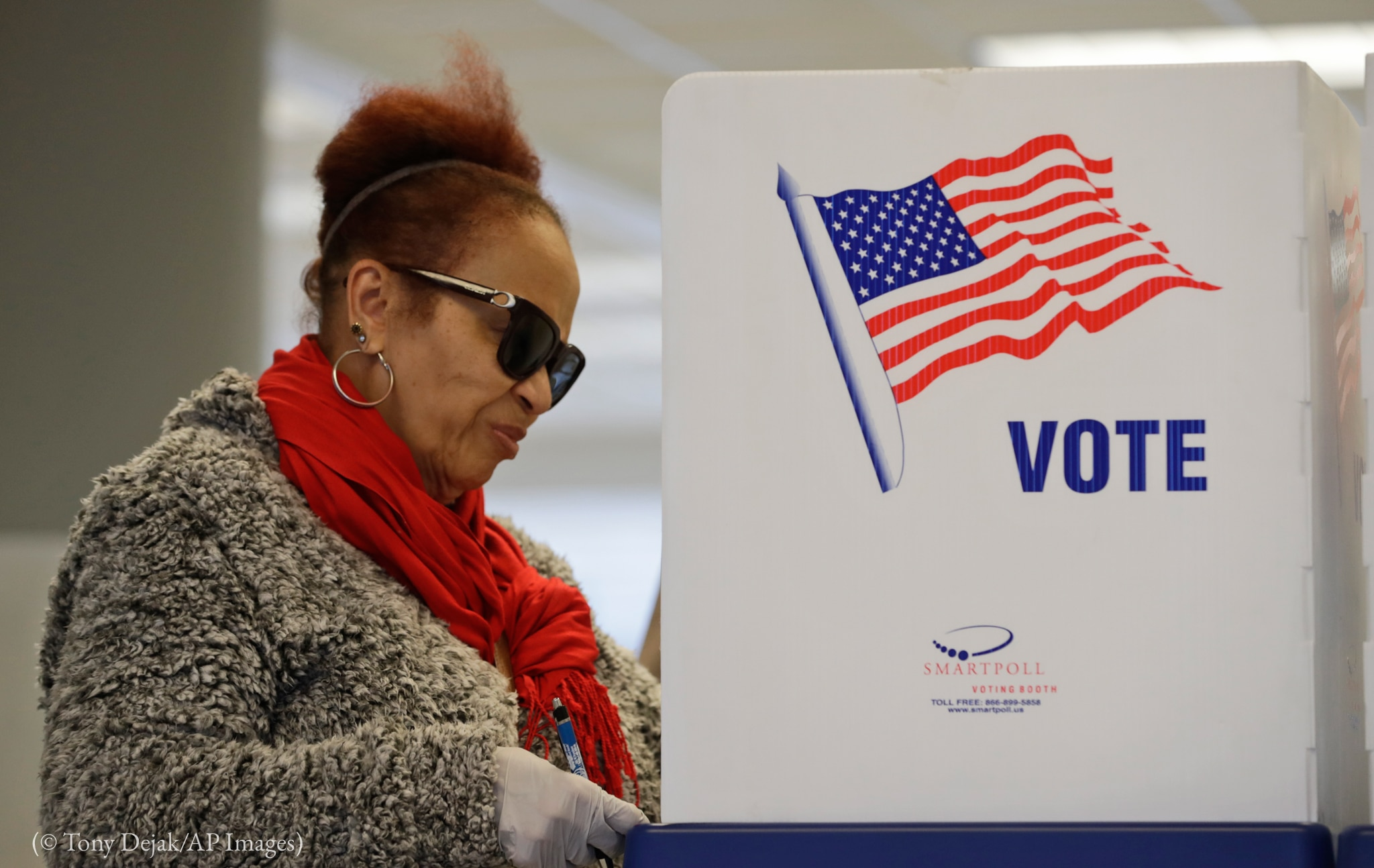 Woman wearing gloves at voting booth (© Tony Dejak/AP Images)