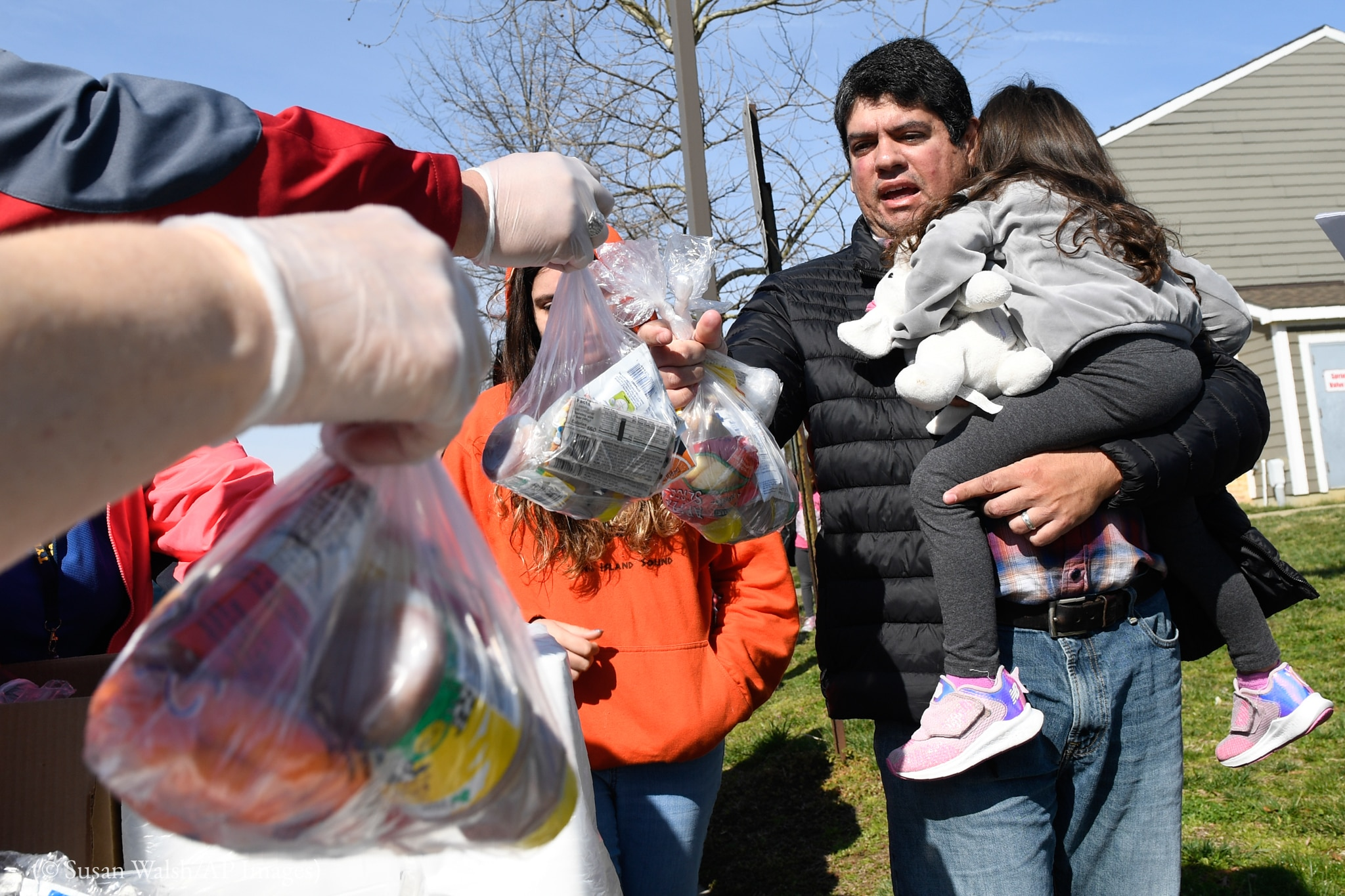 Hombre con un niño en brazos acepta bolsas de plástico llenas de comida de unas manos enguantadas (© Susan Walsh/AP Images)