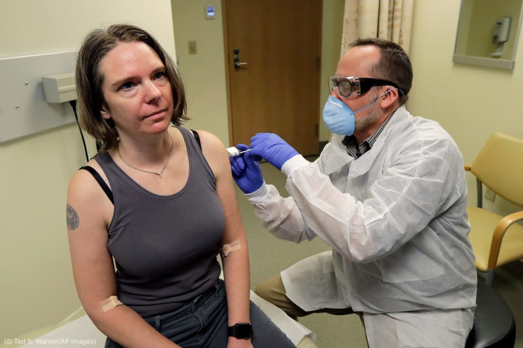 Man in mask vaccinating woman in arm (© Ted S. Warren/AP Images)