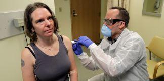 Pria dengan masker menyuntikan vaksin ke lengan wanita (© Ted S. Warren/AP Images