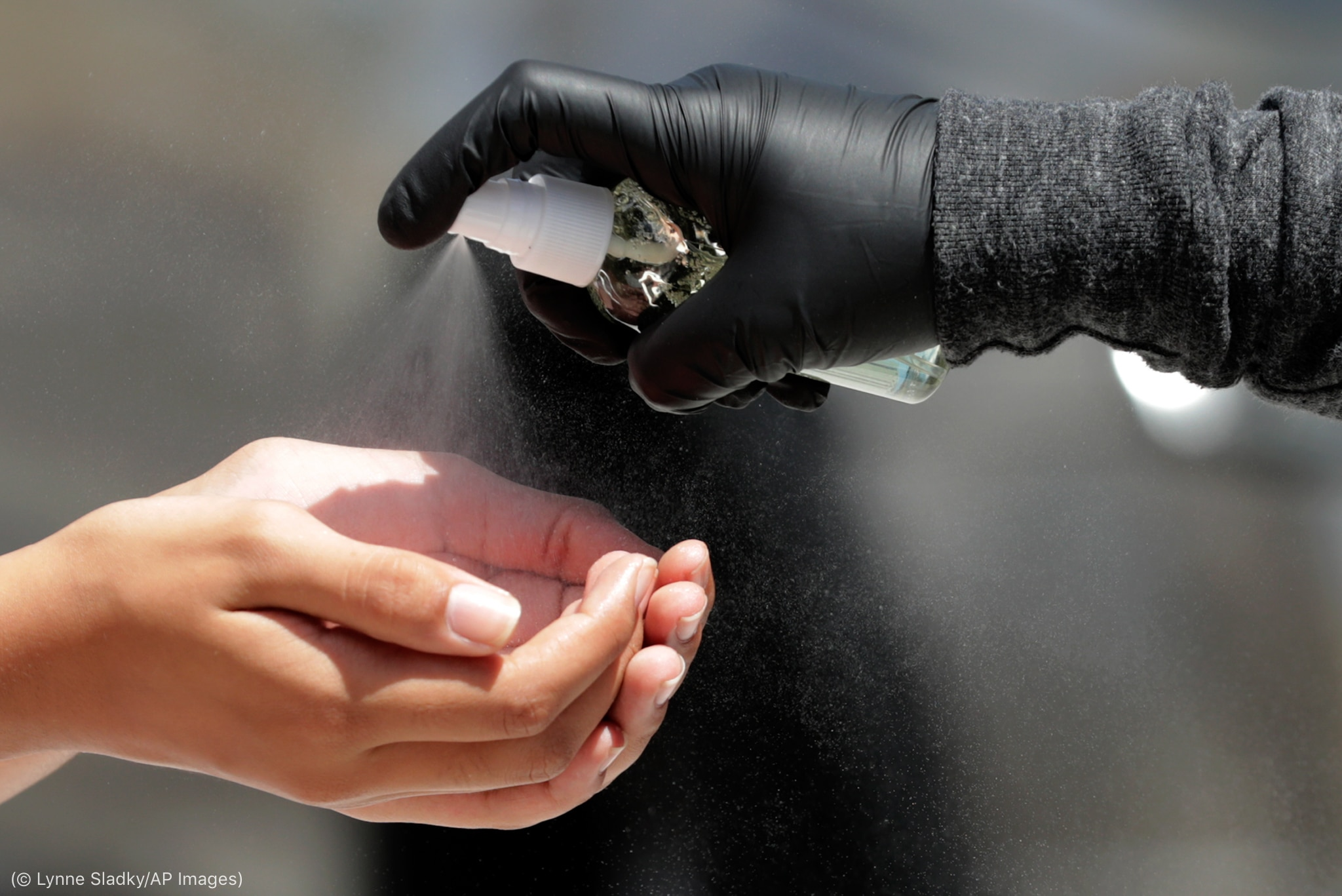 Hand in black glove spraying sanitizer into bare hands of another person (© Lynne Sladky/AP Images)