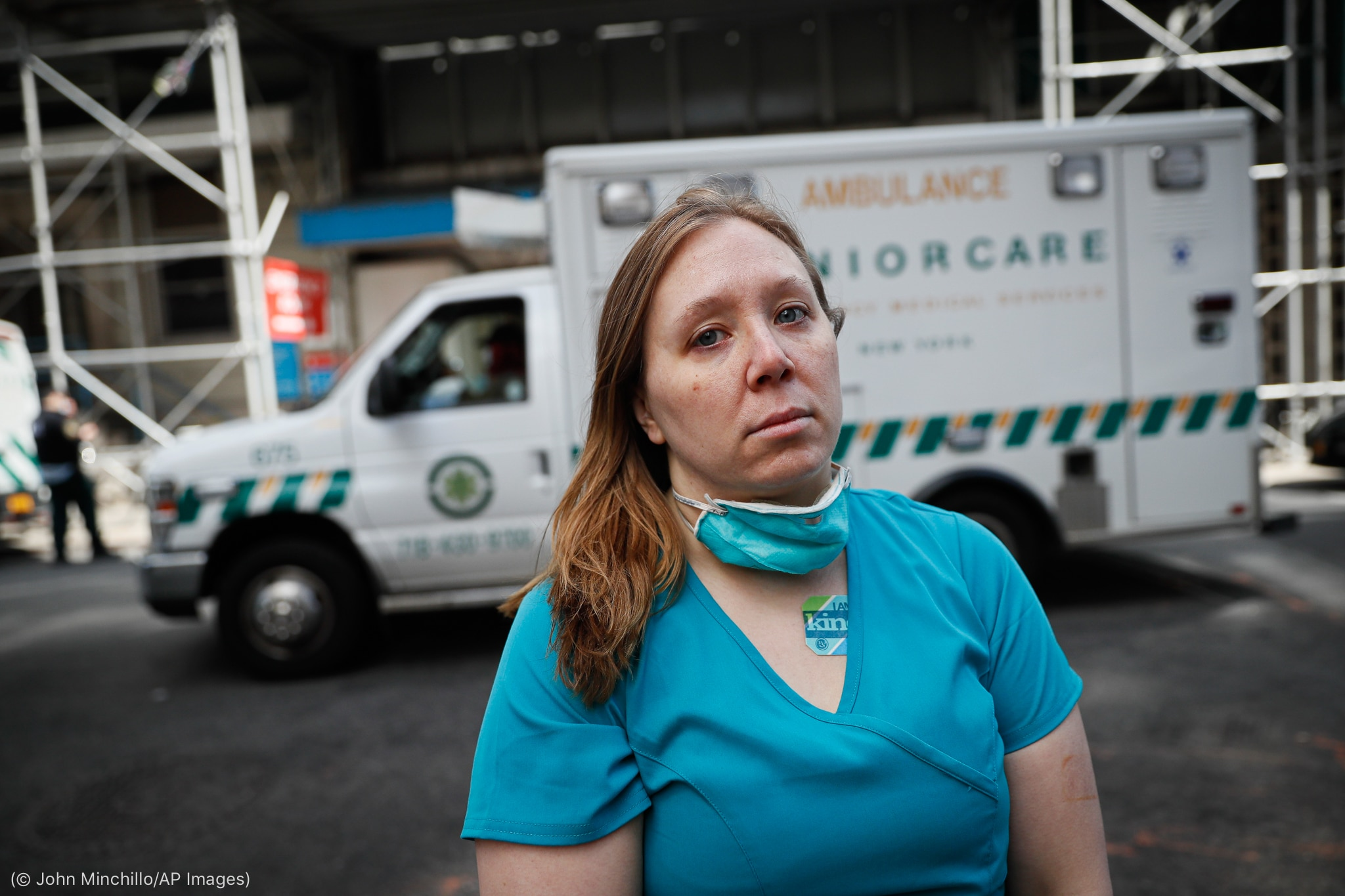 Nurse standing in front of ambulance (© John Minchillo/AP Images)