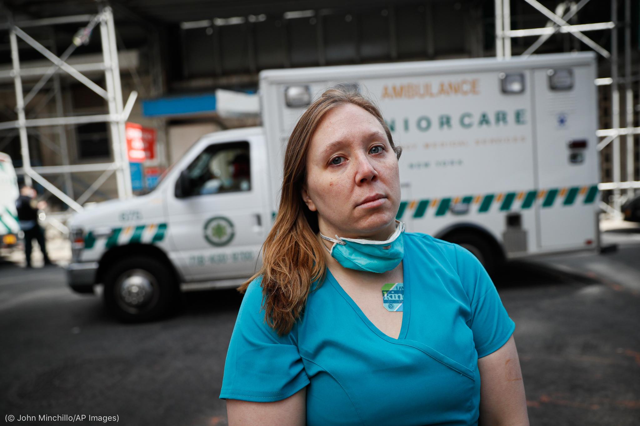 Perawat berdiri di depan mobil ambulans (© John Minchillo/AP Images)