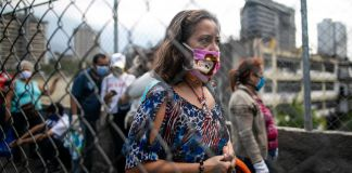Woman standing behind fence wearing a mask (© Ariana Cubillos/AP Images)