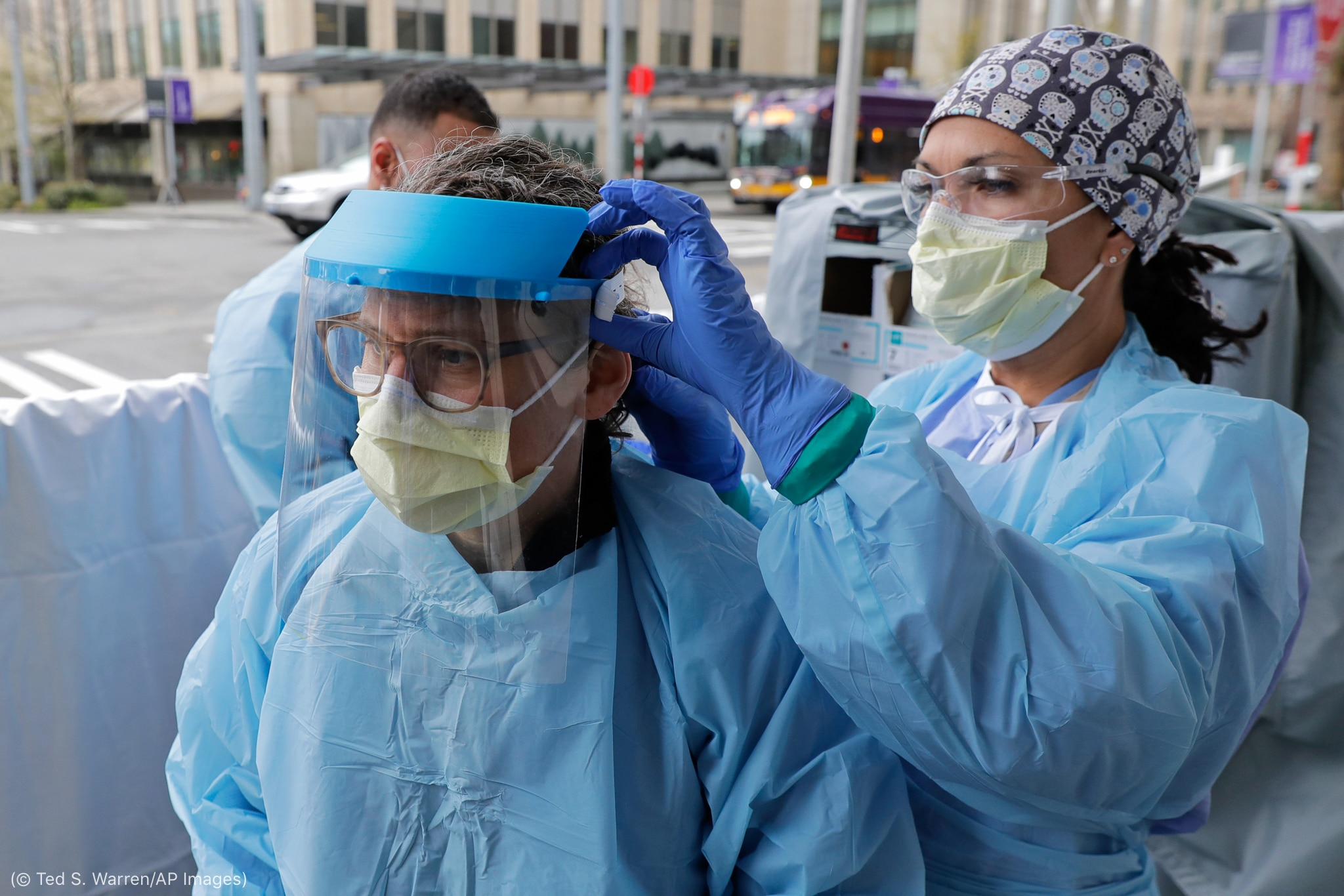 Woman in blue protective gown helping colleague put on face shield (© Ted S. Warren/AP Images)