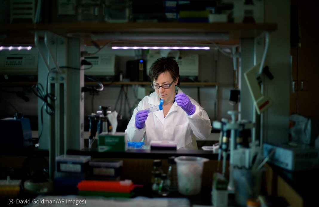 Woman wearing lab coat and gloves looking into vial (© David Goldman/AP Images)