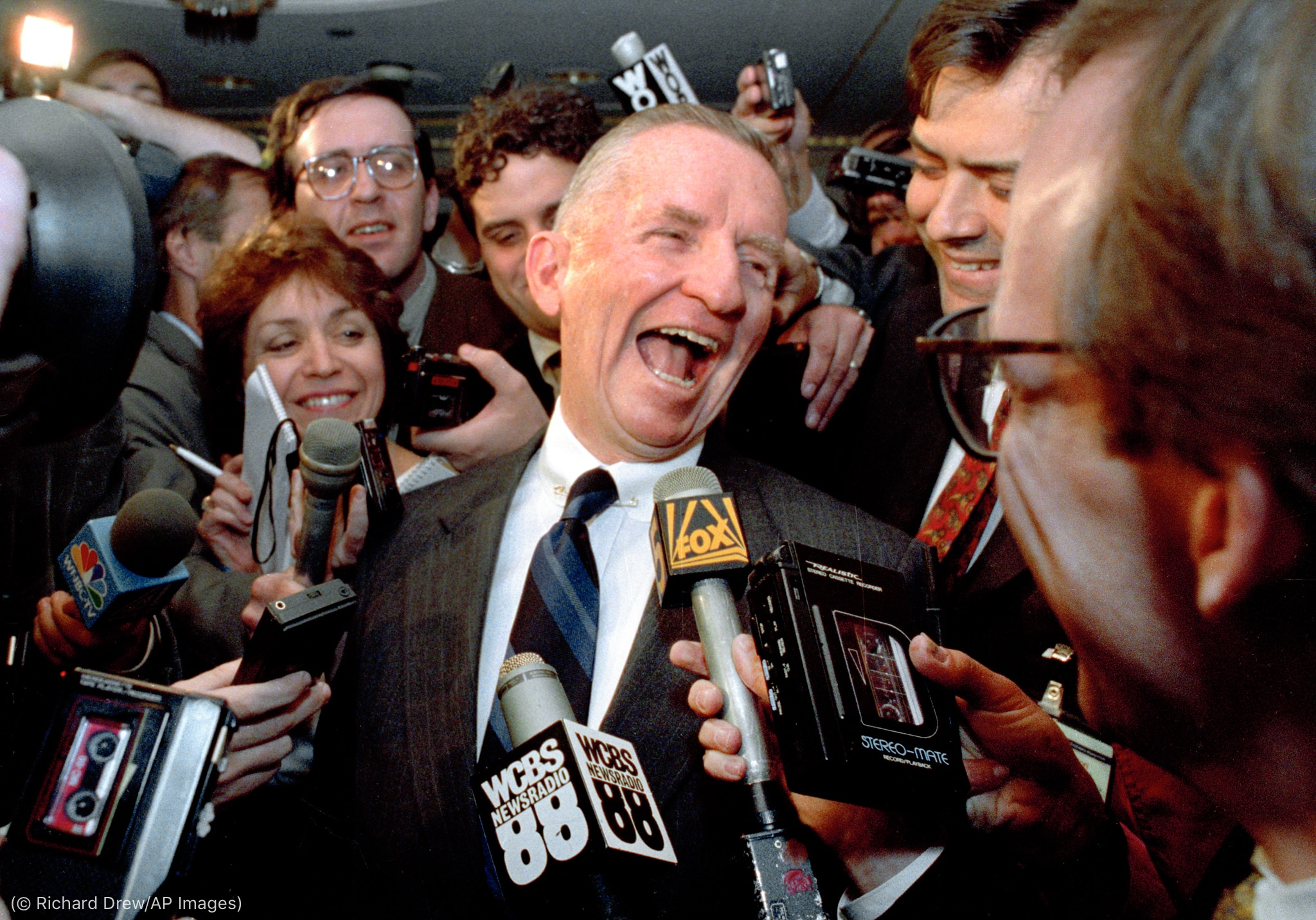 Ross Perot laughing while surrounded by reporters (© Richard Drew/AP Images)