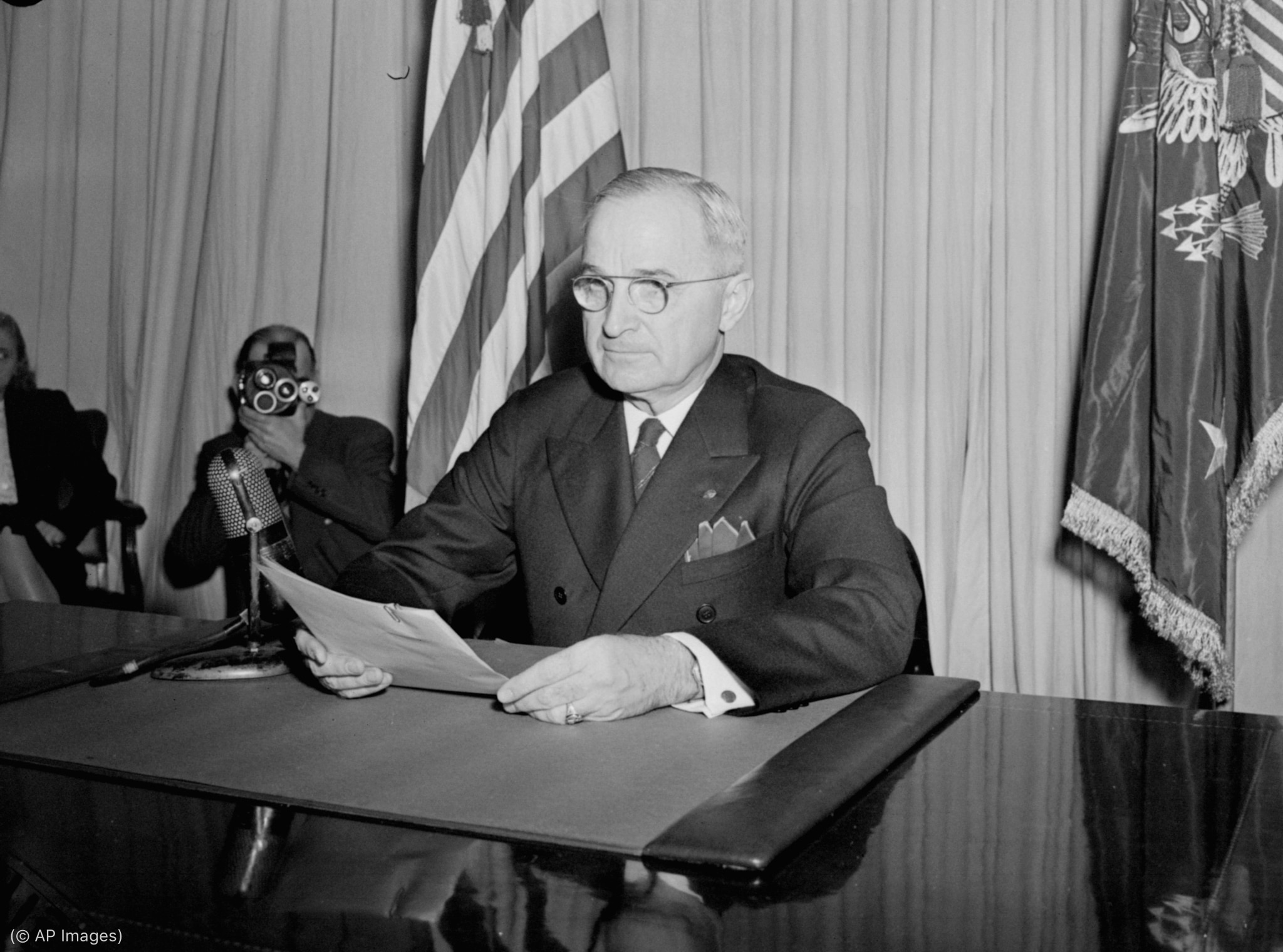 President Truman sitting before a microphone, holding a document (© AP Images)