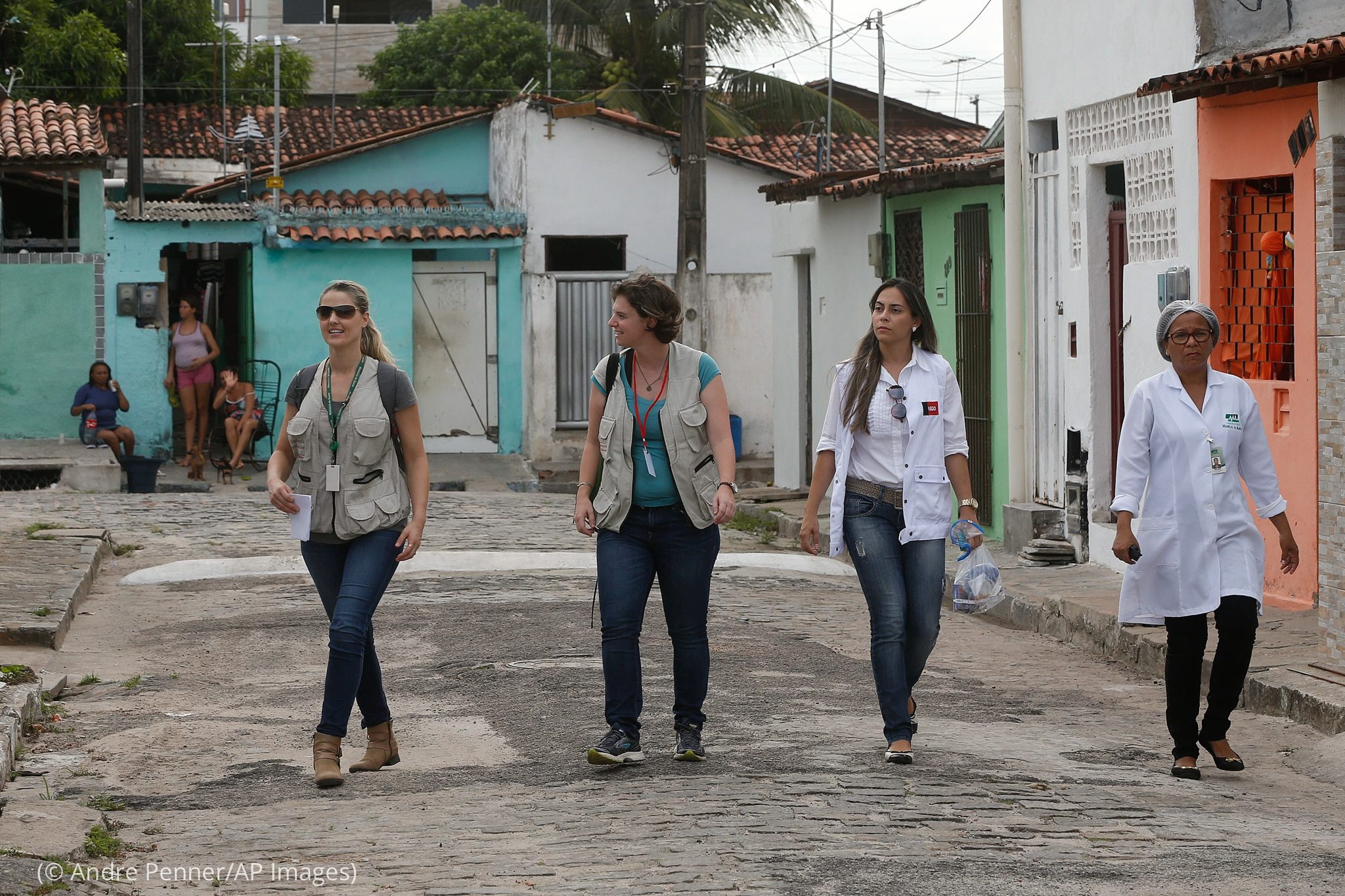 Four women, two in lab coats, walking down street (© Andre Penner/AP Images)