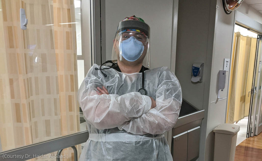 Doctor in protective gear standing with arms crossed in hospital corridor (Courtesy of Dr. Haidar Al-Saadi)
