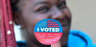 Woman holding an 'I Voted' sticker with translations in many languages (© Frederic J. Brown/AFP/Getty Images)