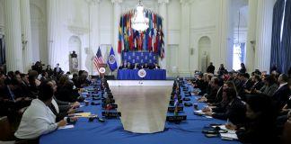 Personas sentadas alrededor de una mesa con banderas (© Chip Somodevilla/Getty Images)