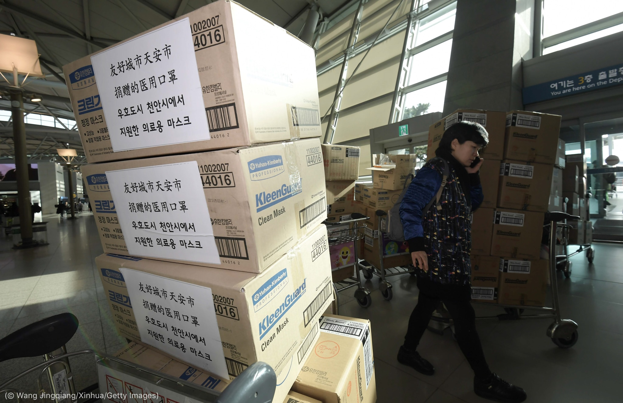 Person walking by stacked boxes (© Wang Jingqiang/Xinhua/Getty Images)