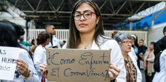 "A doctor holding a sign that reads ""How to face the COVID-19 with no water, protective mask or personnel?(© Leonardo Fernandez Viloria/Getty Images)"