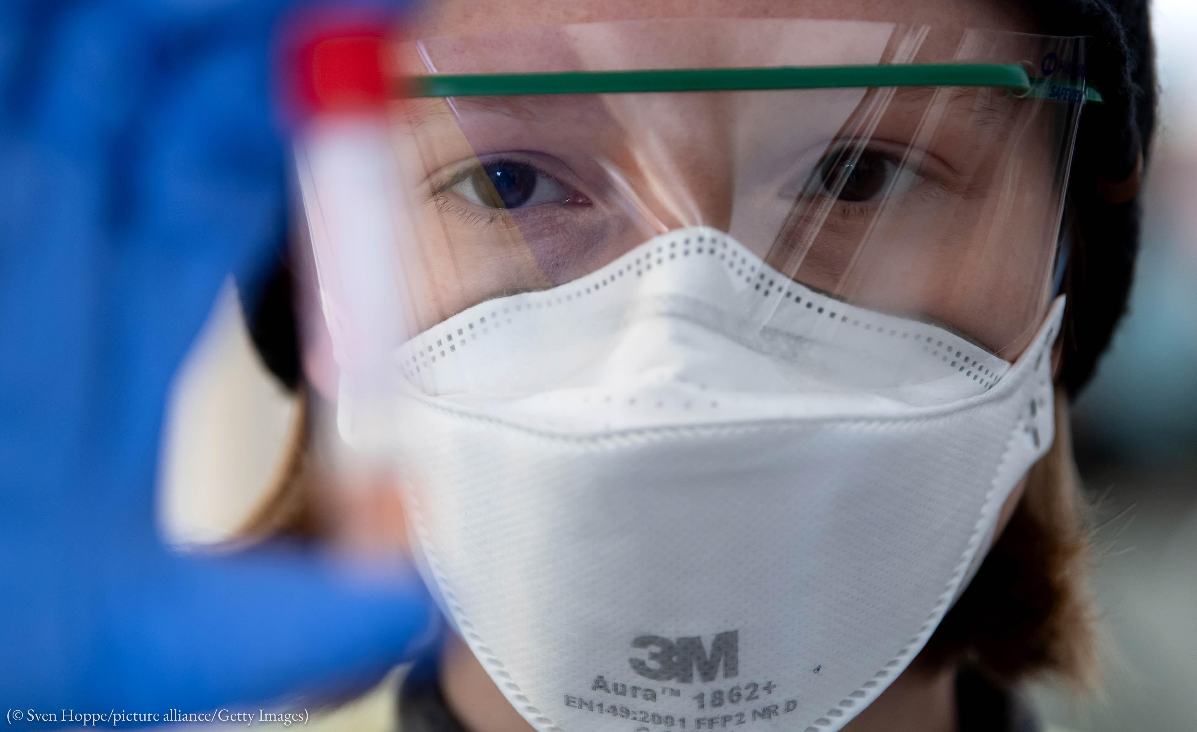 چہرے پر ماسک چڑہائے امتحانی نلکی کو دیکھتا ہوا ایک شخص۔ (Sven Hoppe/picture alliance via Getty Images)