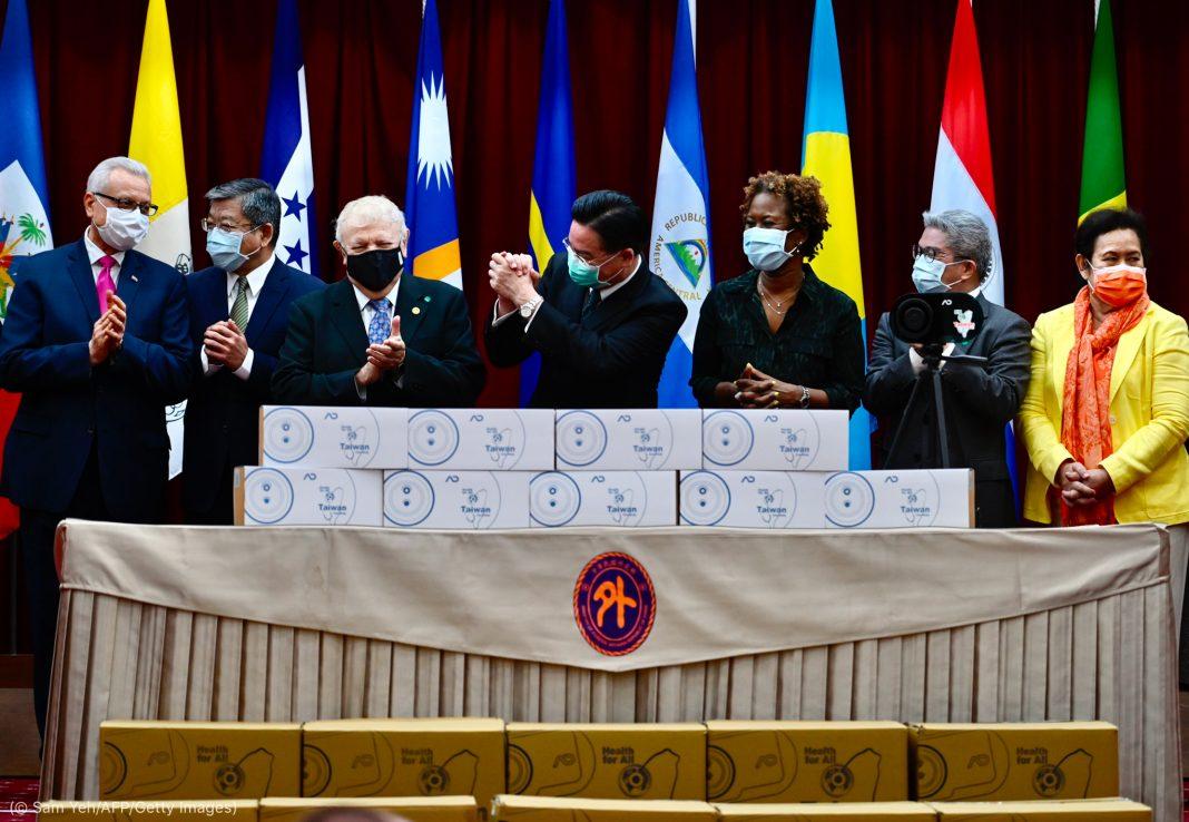 ماسک پہنے لوگ ڈبوں کے پیچھے کھڑے ہیں۔ (© Sam Yeh/AFP/Getty Images)