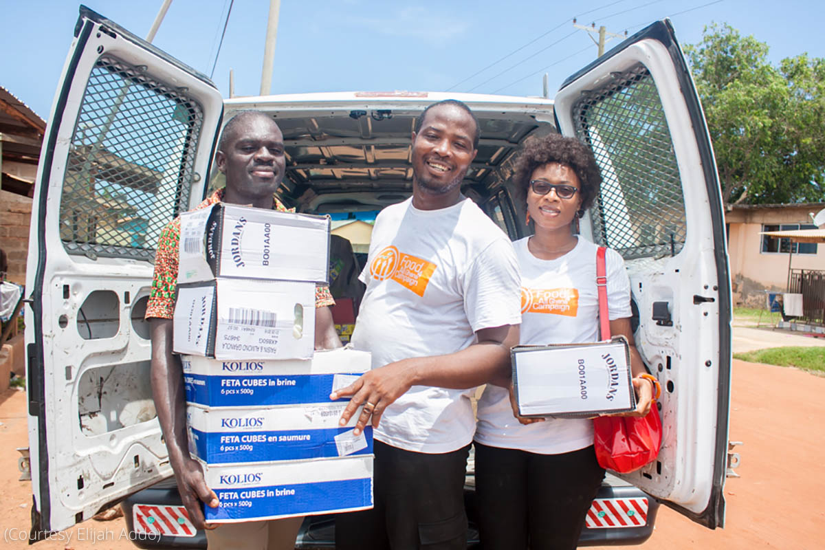 Three people holding boxes at the rear of a van (Courtesy Elijah Addo)