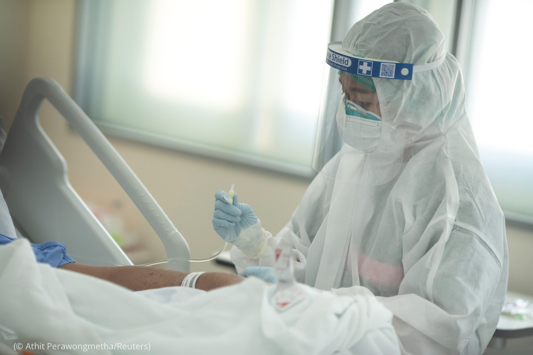 Masked and gowned person checking person in hospital bed (© Athit Perawongmetha/Reuters)