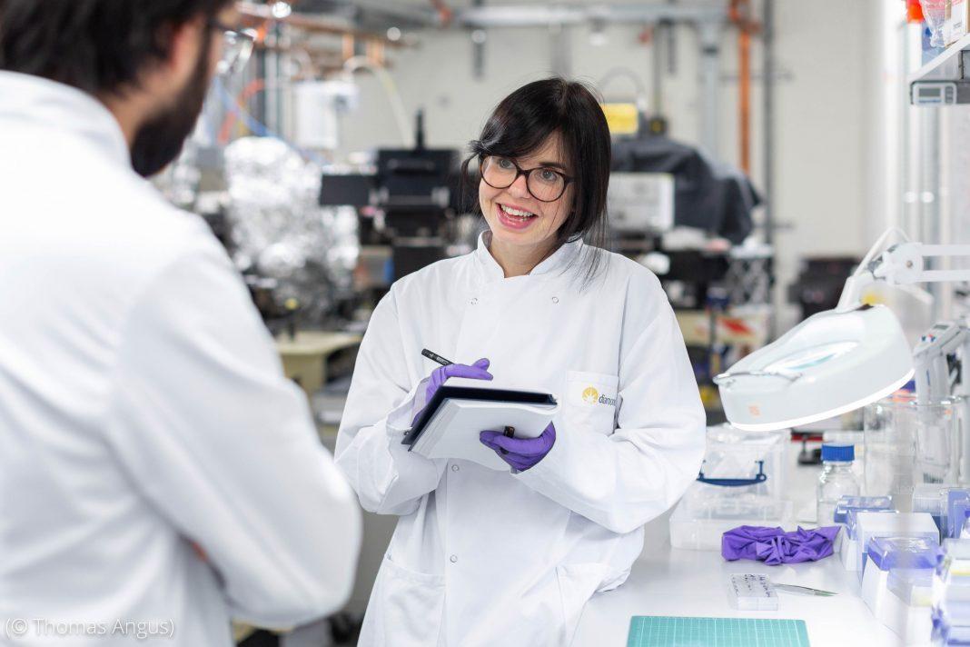 Mulher em laboratório fazendo anotações enquanto conversa com outra pessoa (© Thomas Angus)