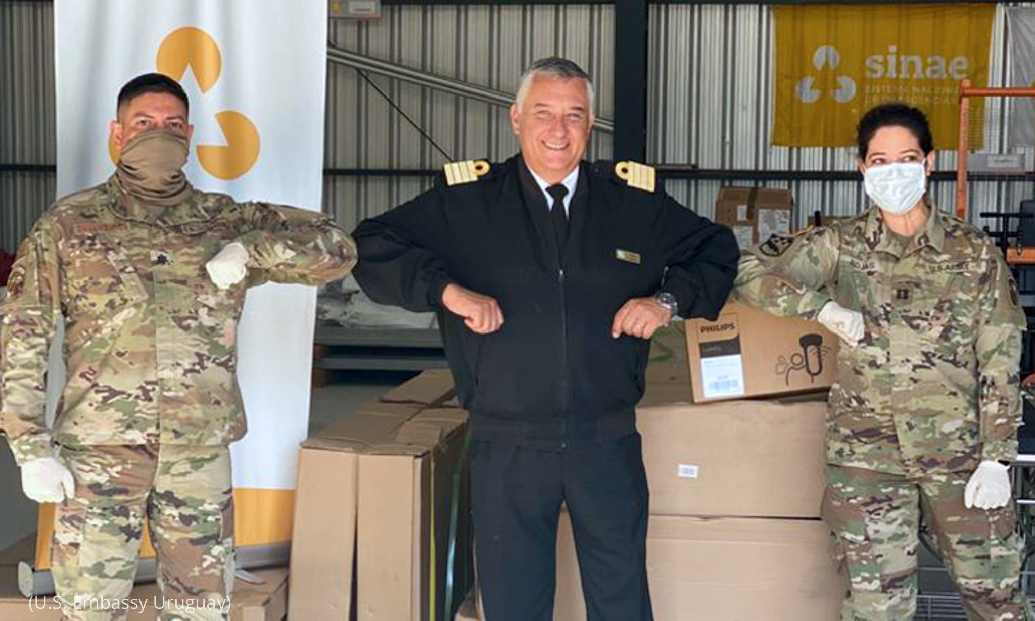 Two masked and gloved soldiers touching elbows with officer in front of boxes of equipment (U.S. Embassy Uruguay)