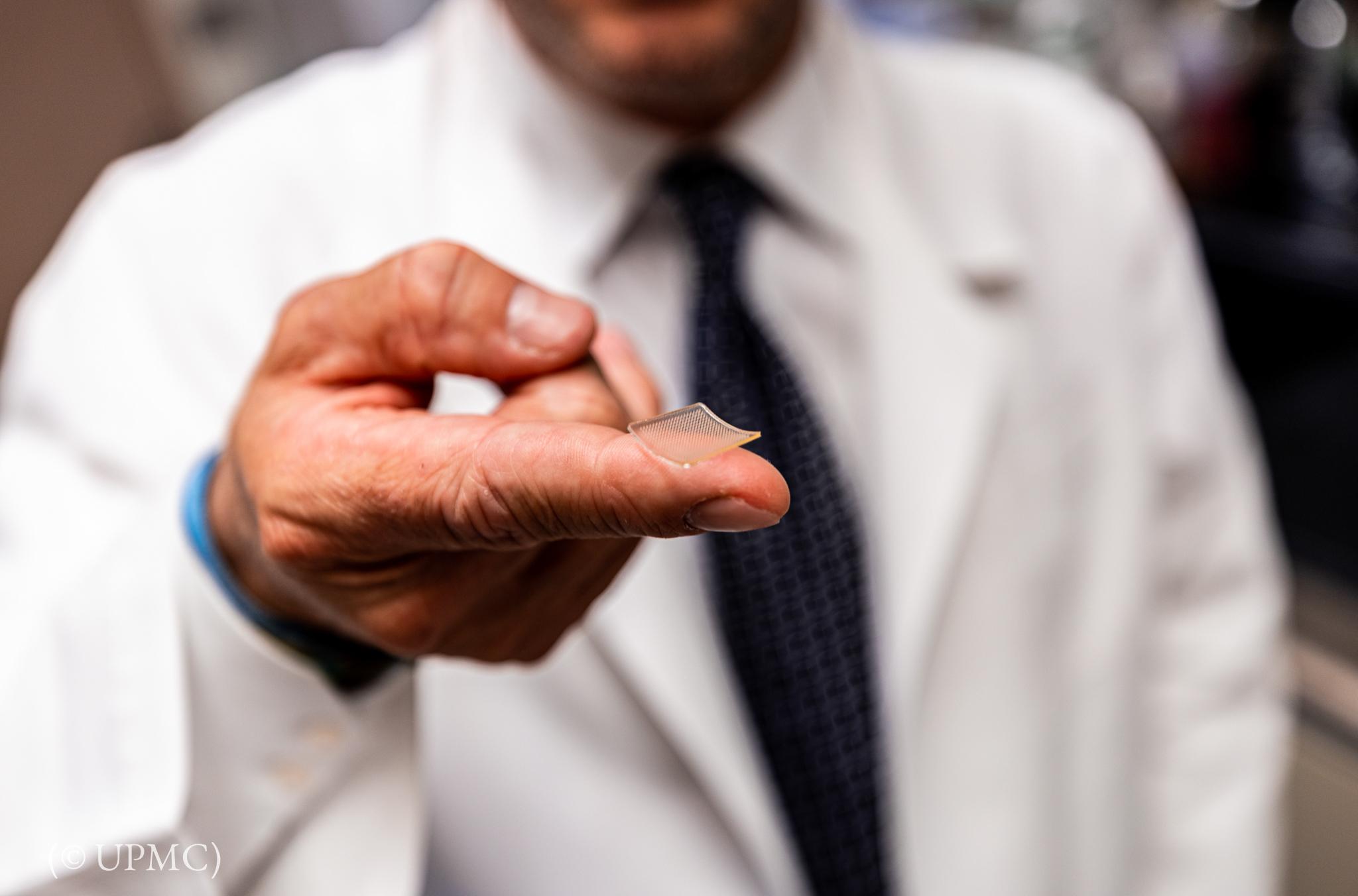 ایک آدمی کی انگلی پر مربع شکل کا چھوٹا سا ایک ٹکڑا۔ (© UPMC)