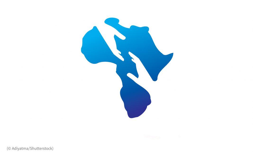 Ilustración de África con un perfilado de manos que se extienden a través del continente (© Adiyatma/Shutterstock)