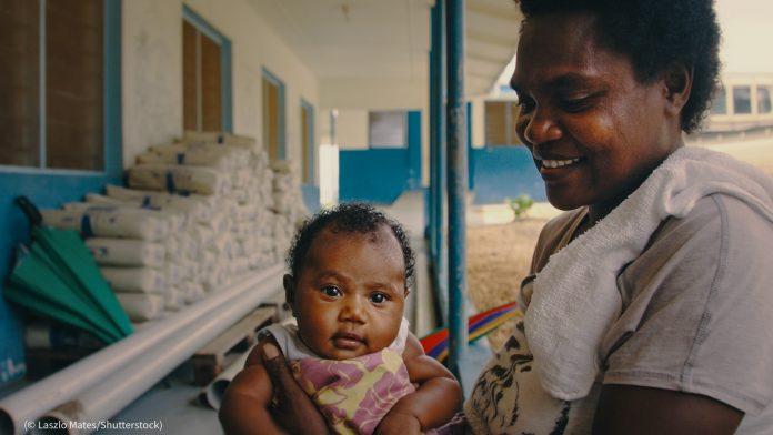 Woman holding baby (© Laszlo Mates/Shutterstock)