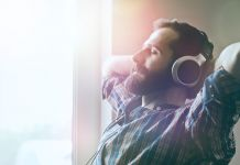 Man sitting by window while wearing headphones (© Shutterstock)